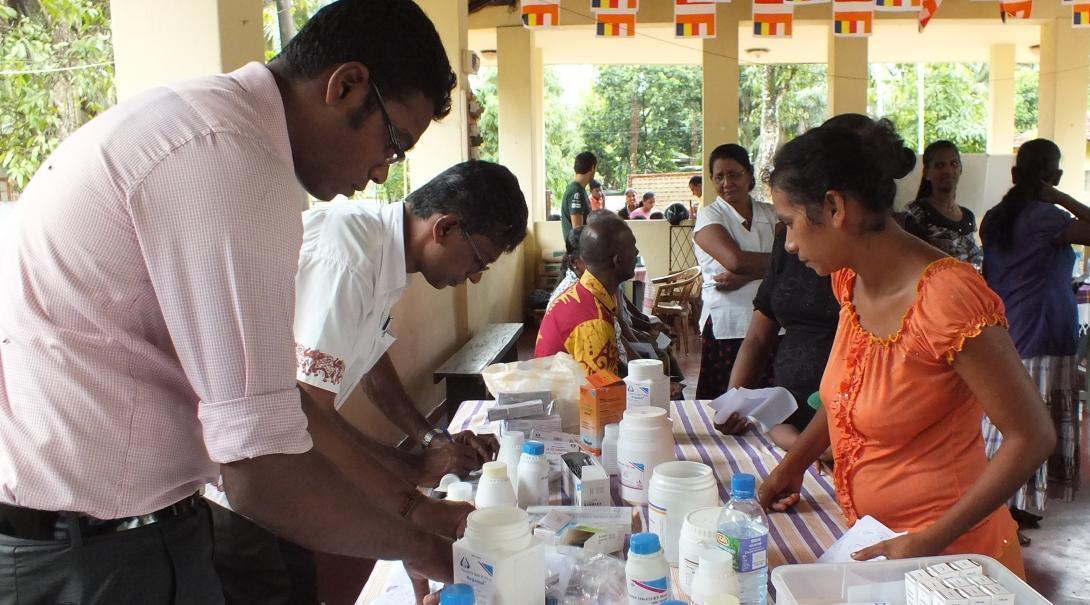 Interno médico ayuda a doctor a entregar medicamentos durante sus prácticas en Sri Lanka.
